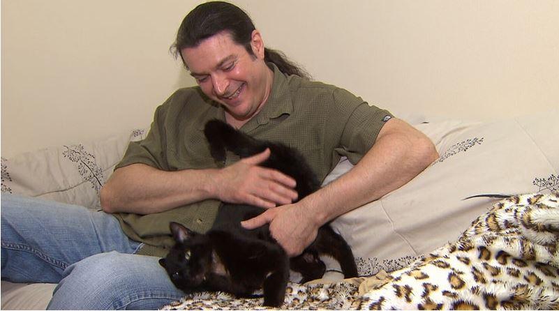 Gatto nero che gioca con un uomo