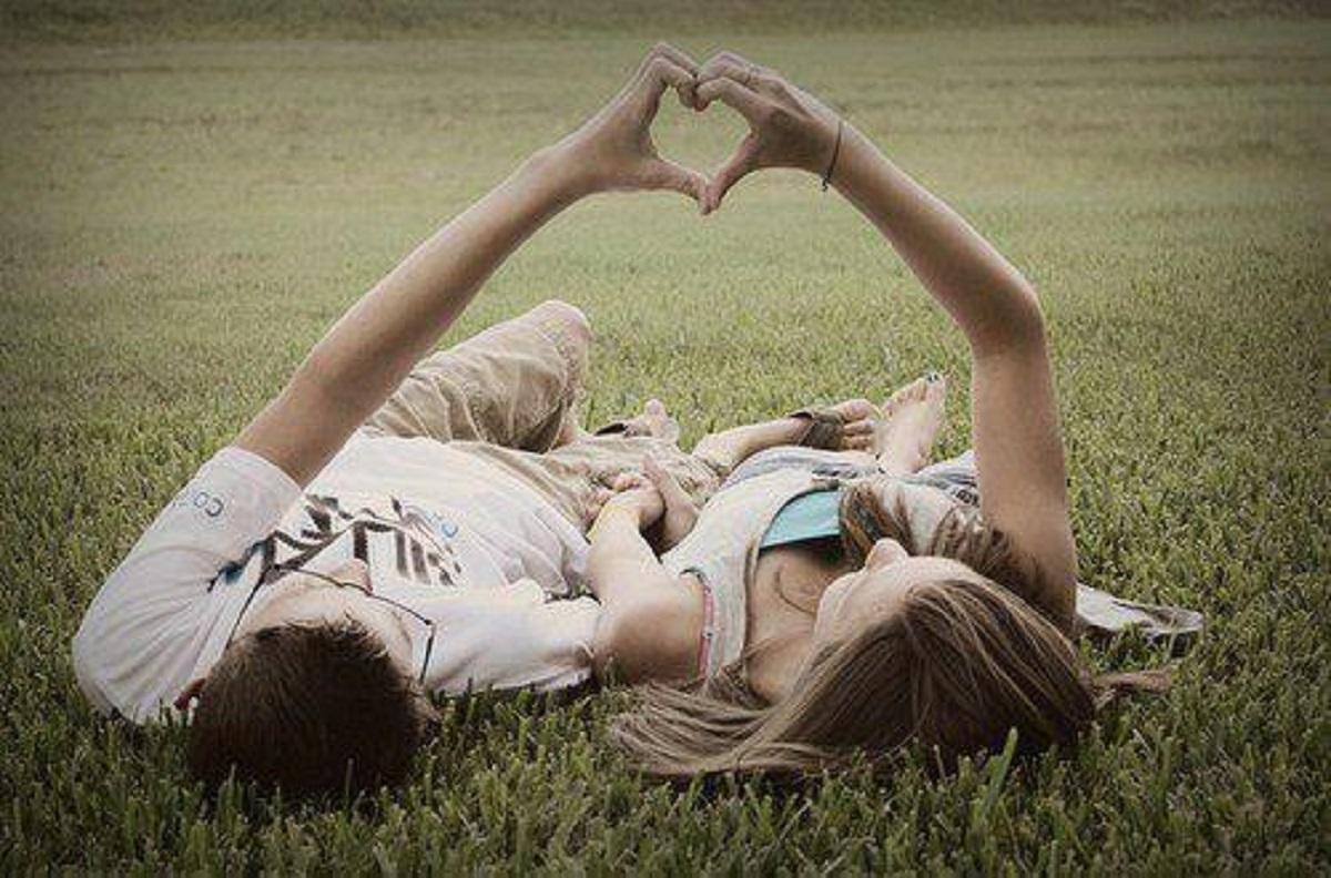 coppia di innamorati che formano un cuore con le mani
