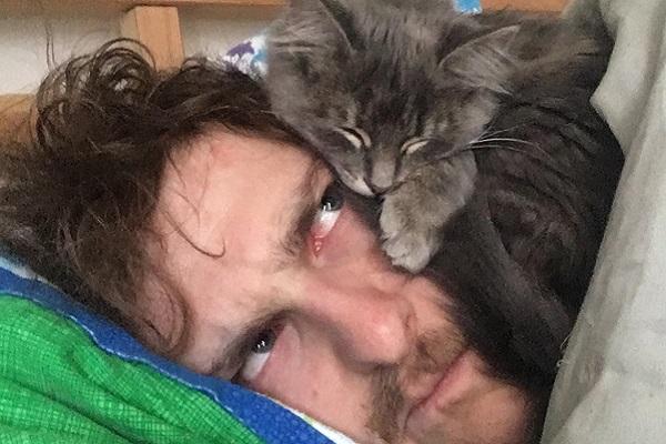 uomo guarda gattino che gli dorme in testa