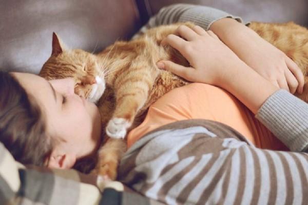 ragazza dorme con il suo gatto