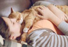 donna abbraccia gatto che dorme