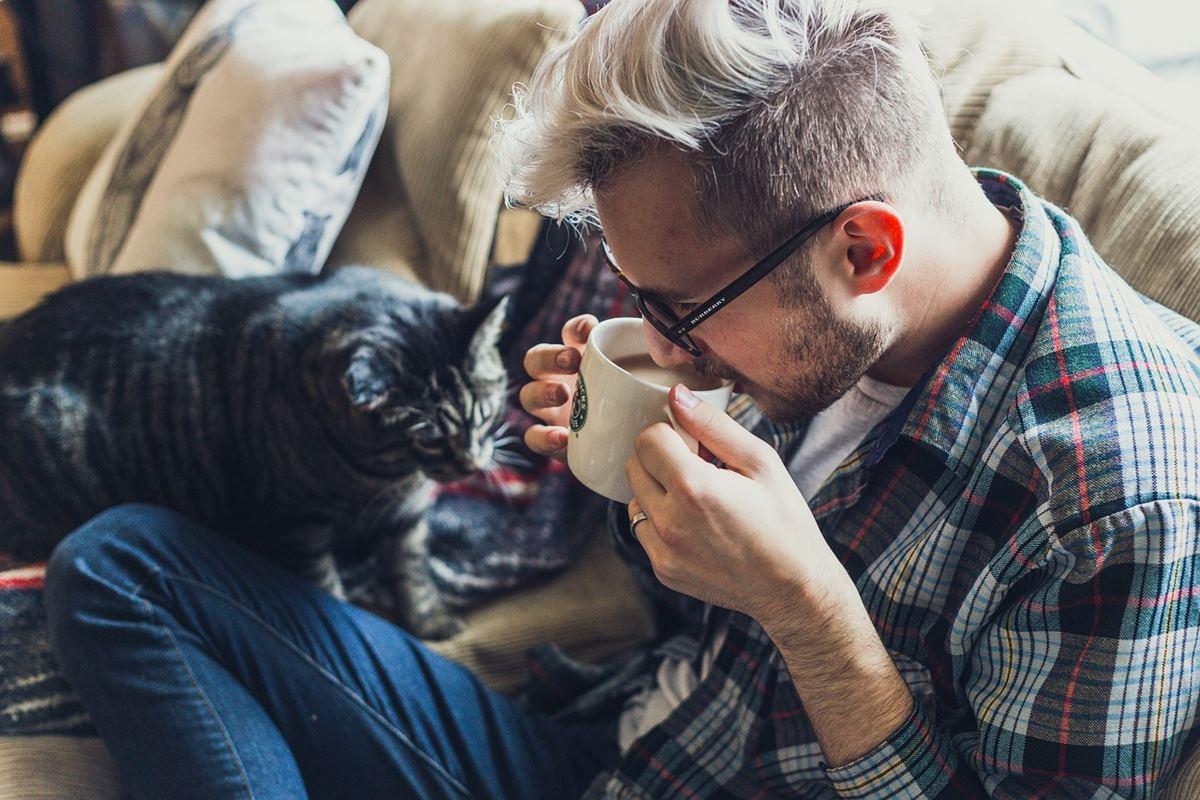 ragazzo beve un tè con il gatto