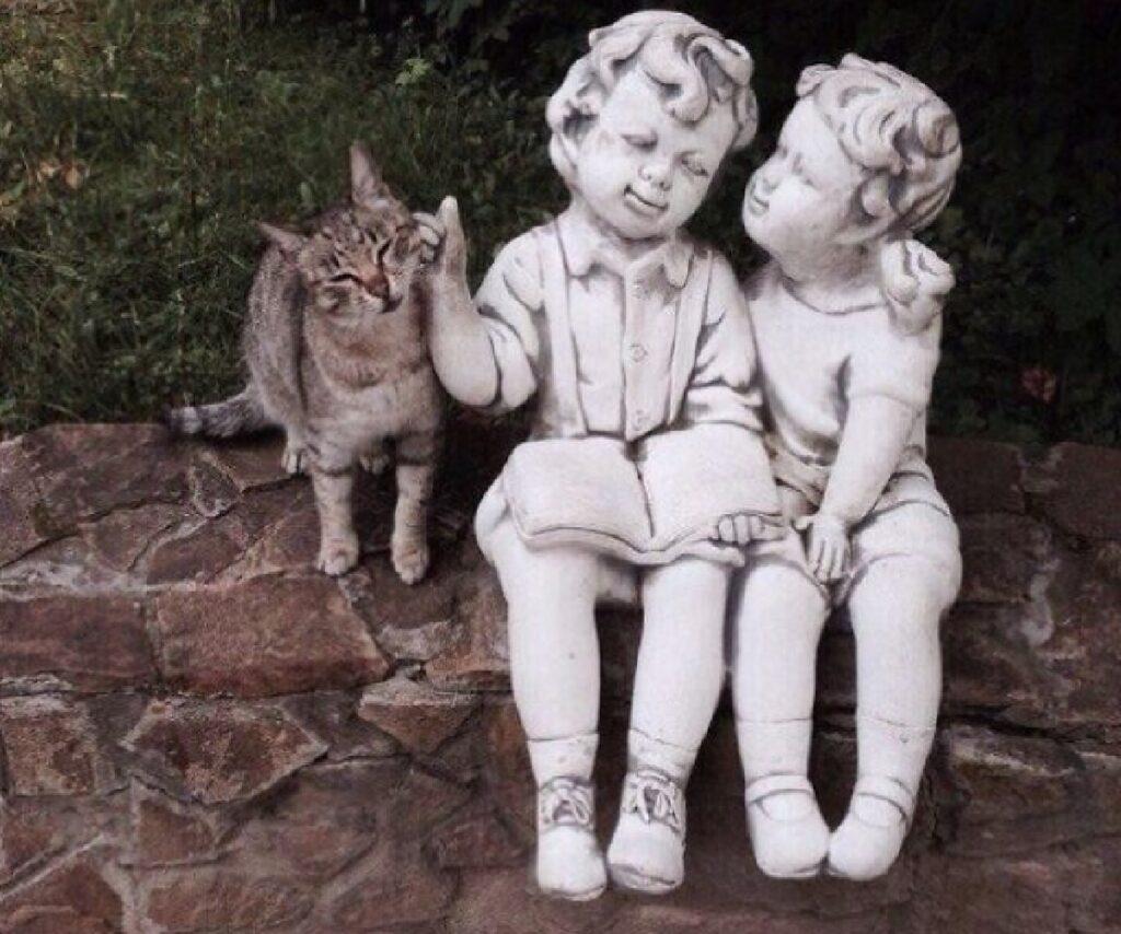 gatto carezze da due statue