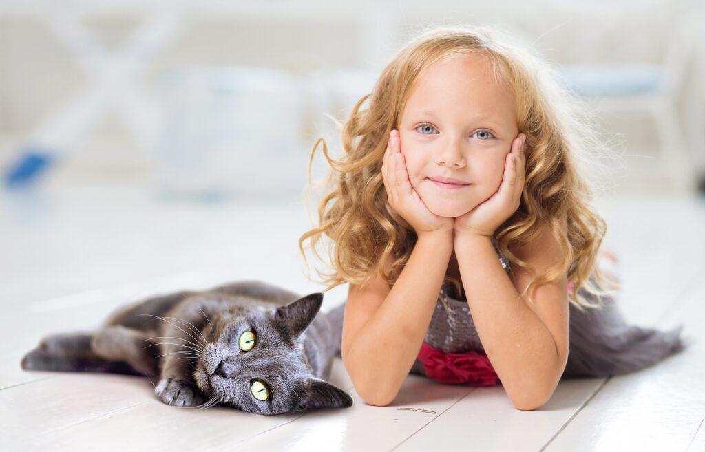 gatto sdraiato accanto ad una bimba