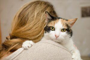 donna di spalle tiene un gatto in braccio
